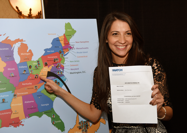 A graduating female at WVU School of Medicine points to Kentucky as her residency location during the annual Match Day ceremony.